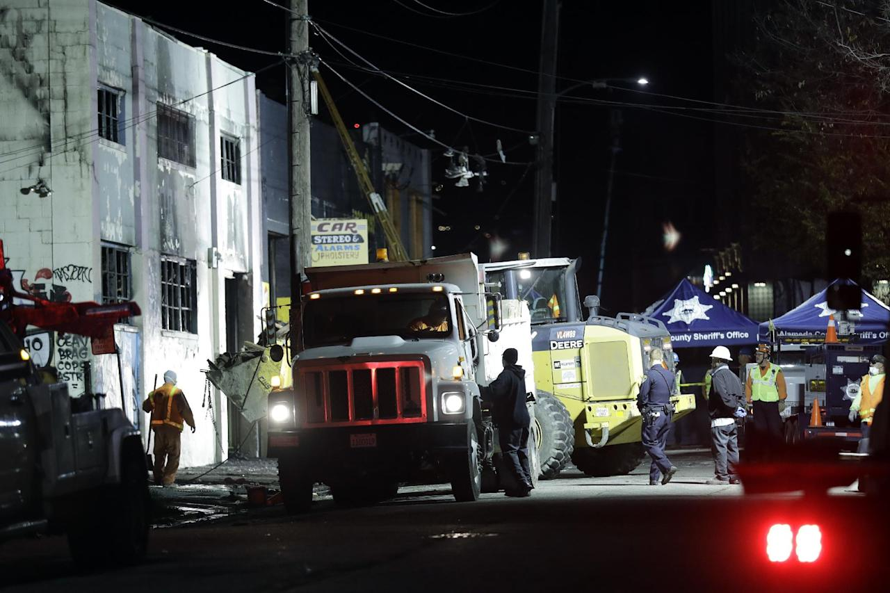 Emergency crews perform clean up in the aftermath of a warehouse fire Saturday, Dec. 3, 2016, in Oakland, Calif. Firefighters struggled to get to bodies in the rubble Saturday, after a deadly fire tore through a converted Oakland warehouse during a late-night electronic music party Friday, making the charred structure unsafe for emergency crews to enter. (AP Photo/Marcio Jose Sanchez)