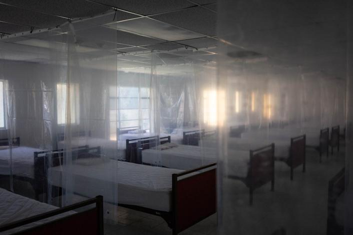 """The Our Lady of Guadalupe men's shelter in Calexico, Calif., temporarily closed after seven of the 20 men staying there caught COVID-19. The shelter has since spaced beds farther apart and hung plastic dividers. <span class=""""copyright"""">(Anna Maria Barry-Jester / Kaiser Health News)</span>"""
