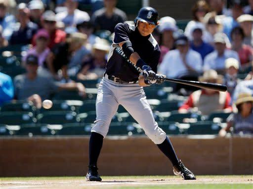Seattle Mariners' Munenori Kawasaki hits an infield singe against the Colorado Rockies during the first inning of a spring training baseball game Tuesday, April 3, 2012, in Scottsdale, Ariz. (AP Photo/Marcio Jose Sanchez)