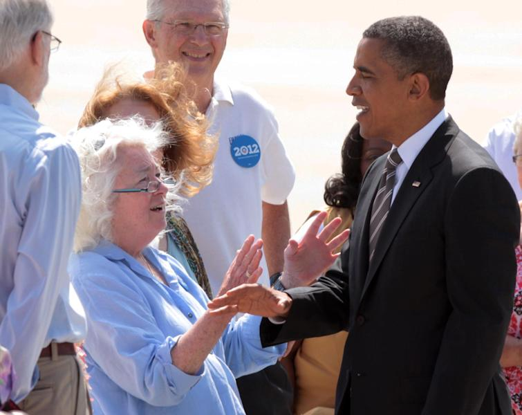 President Barack Obama is greeted after arriving on Air Force One at the Eastern Iowa Airport in Cedar Rapids, Iowa, Tuesday July 10, 2012. (AP Photo/Conrad Schmidt)