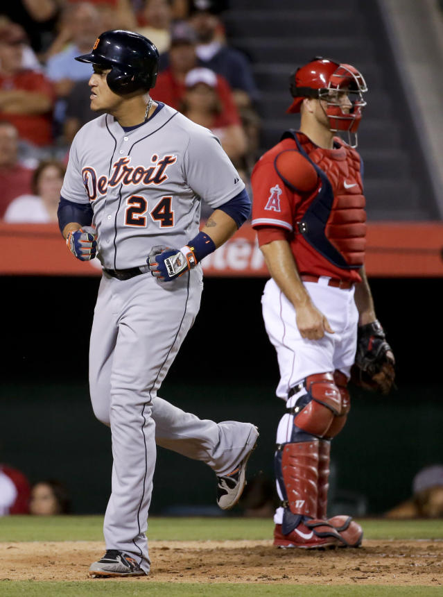 Detroit Tigers' Miguel Cabrera, left, runs past Los Angeles Angels catcher Chris Iannetta after hitting a home run during the fourth inning of a baseball game in Anaheim, Calif., Friday, July 25, 2014. (AP Photo/Chris Carlson)