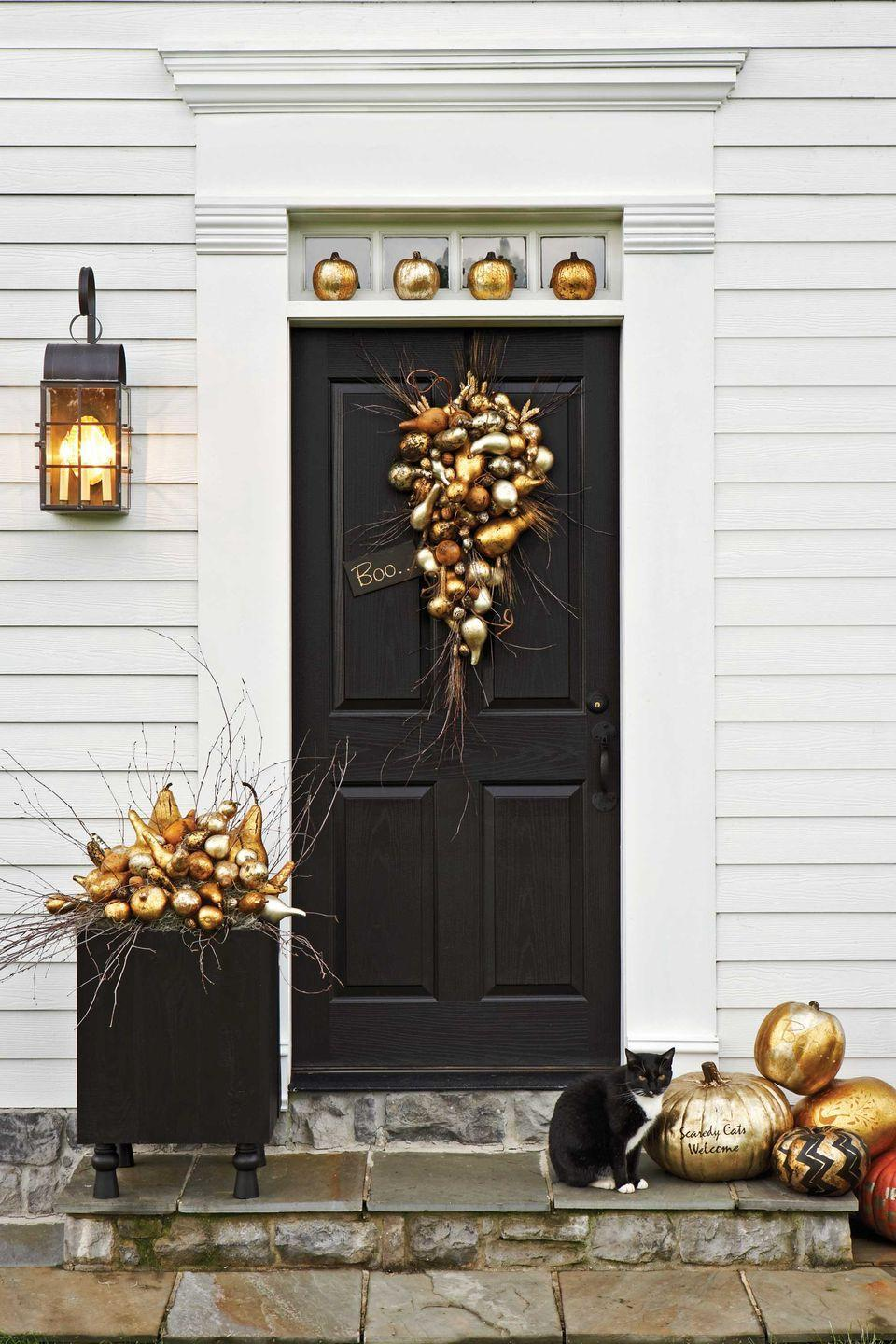 """<p>What's it take to achieve this shimmering display? Gourds, pumpkins, and a gilding kit! When all these metallic colors come together, your entrance will turn into one hot spot.</p><p><strong><a href=""""https://www.countryliving.com/diy-crafts/how-to/g616/how-to-guild-a-pumpkin/"""" rel=""""nofollow noopener"""" target=""""_blank"""" data-ylk=""""slk:Get the tutorial"""" class=""""link rapid-noclick-resp"""">Get the tutorial</a>.</strong> </p>"""