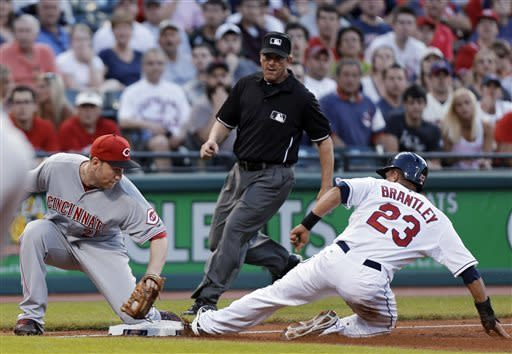 Cleveland Indians' Michael Brantley (23) beats the tag from Cincinnati Reds third baseman Todd Frazier to steal third in the fourth inning of a baseball game Thursday, May 30, 2013, in Cleveland. Umpire Jeff Kellogg moves in to make the call(AP Photo/Mark Duncan)