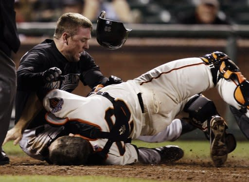 FILE - In this May 25, 2011, file photo, Florida Marlins' Scott Cousins, top, collides with San Francisco Giants catcher Buster Posey on a fly ball hit by Marlins' Emilio Bonifacio during the 12th inning of a baseball game in San Francisco. Posey wants all players protected from hard collisions at home plate and serious injuries, baserunners and catchers alike, whether Major League Baseball implements a new rule banning home-plate collisions in time for the 2014 season. (AP Photo/Marcio Jose Sanchez, File)