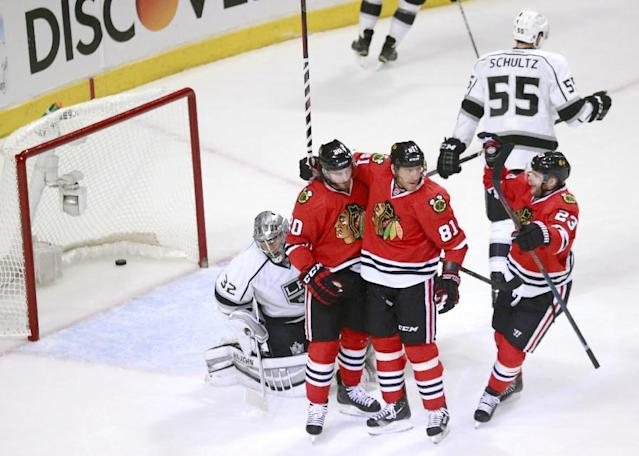 Chicago Blackhawks left wing Brandon Saad (20), Marian Hossa (81) and Kris Versteeg (23) celebrate Saad's goal against Los Angeles Kings goalie Jonathan Quick (32) as Jeff Schultz (55) skates away during the first period of Game 1 of the Western Conference finals in the NHL hockey Stanley Cup playoffs in Chicago on Sunday, May 18, 2014. (AP Photo/Charles Rex Arbogast)