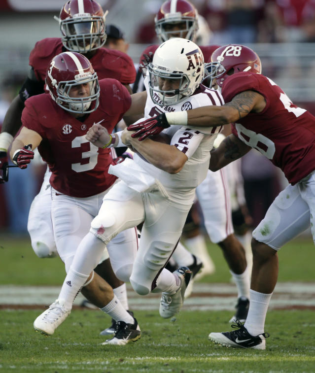 Texas A&M quarterback Johnny Manziel (2) is stopped after a first down run by Alabama defensive back Dee Milliner (28) and defensive back Vinnie Sunseri (3)during the first half of an NCAA college football game at Bryant-Denny Stadium in Tuscaloosa, Ala., Saturday, Nov. 10, 2012. (AP Photo/Dave Martin)