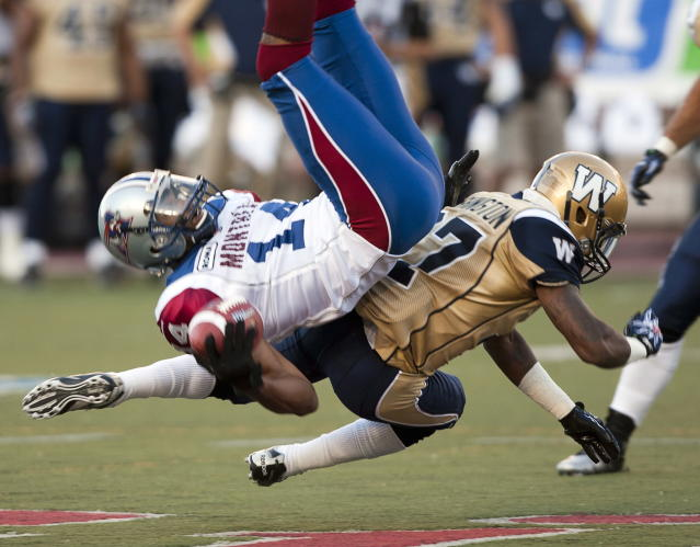 Montreal Alouettes receiver Brandon London, left, is tackled by Winnipeg Blue Bombers Demond Washington during first quarter Canadian Football League pre-season action Thursday, June 14, 2012 in Montreal. THE CANADIAN PRESS/Ryan Remiorz