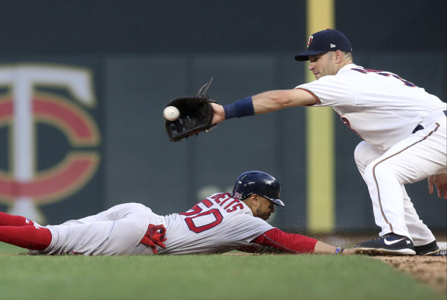 Boston Red Sox' Mookie Betts, left, beats the throw to Minnesota Twins first baseman Joe Mauer on a pickoff attempt during the fifth inning of a baseball game Tuesday, June 19, 2018, in Minneapolis. (AP Photo/Jim Mone)