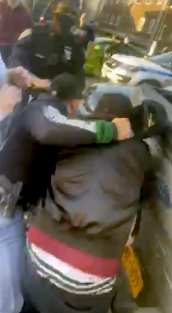 """In this April 29, 2020 image made from video provided by Adegoke Atunbi, a New York City Police Officer in plain clothes wrestles a man to the ground while making an arrest in the Brooklyn borough of New York. The video is among those posted on social media recently that show the NYPD using physical force while out enforcing the city's 6-foot-of-distance social distance rule. Despite mounting pressure from watchdogs to stop using police to enforce social distancing, Mayor Bill de Blasio stood by the practice on Thursday, saying: """"We're not going to sideline the NYPD."""" (Adegoke Atunbi via AP)"""