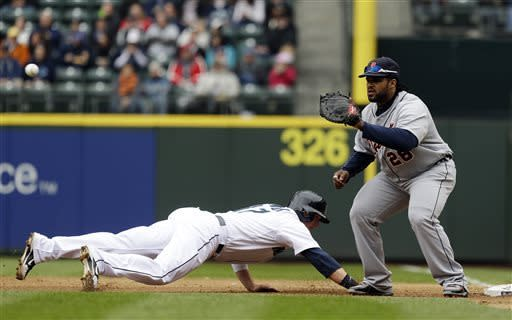 Seattle Mariners' Justin Smoak dives back to first base ahead of the pick-off attempt to Detroit Tigers first baseman Prince Fielder, right, in the fourth inning of a baseball game, Thursday, April 18, 2013, in Seattle. (AP Photo/Ted S. Warren)