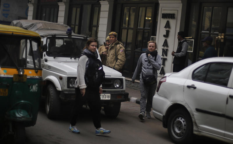 Foreign tourists walk past Delhi police officers in a neighborhood which houses hundreds of budget hotels in New Delhi, India, Wednesday, Jan. 15, 2014. A Danish tourist was gang-raped Tuesday evening near a popular central shopping area in the Indian capital after she lost her way and asked for directions back to her hotel, police said Wednesday. The attack is the latest case to focus international attention on the scourge of rape and violence against women in India. (AP Photo/Altaf Qadri)