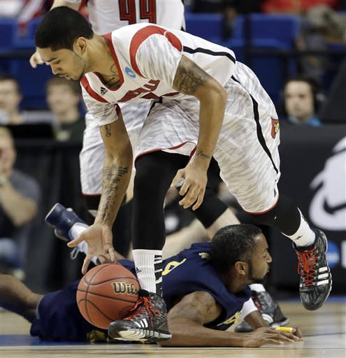 Louisville guard Peyton Siva (3) scoops the ball up after stealing it from North Carolina A&T forward DaMetrius Upchurch (4) during the second half of a second-round game in the NCAA college basketball tournament, Thursday, March 21, 2013, in Lexington, Ky. Louisville won 79-48. (AP Photo/John Bazemore)