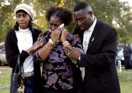 FILE - In this Tuesday, March 14, 2006 file photo, Gina Jones, center, mother of 14-year-old Martin Lee Anderson, is comforted by her sister, Debbie Williams, and attorney Benjamin Crump, after reburying her son in Panama City, Fla. Jones said Tuesday she wants justice now that a second autopsy showed that he did not die from a blood disorder as a medical examiner initially ruled. (AP Photo/Mari Darr-Welch)