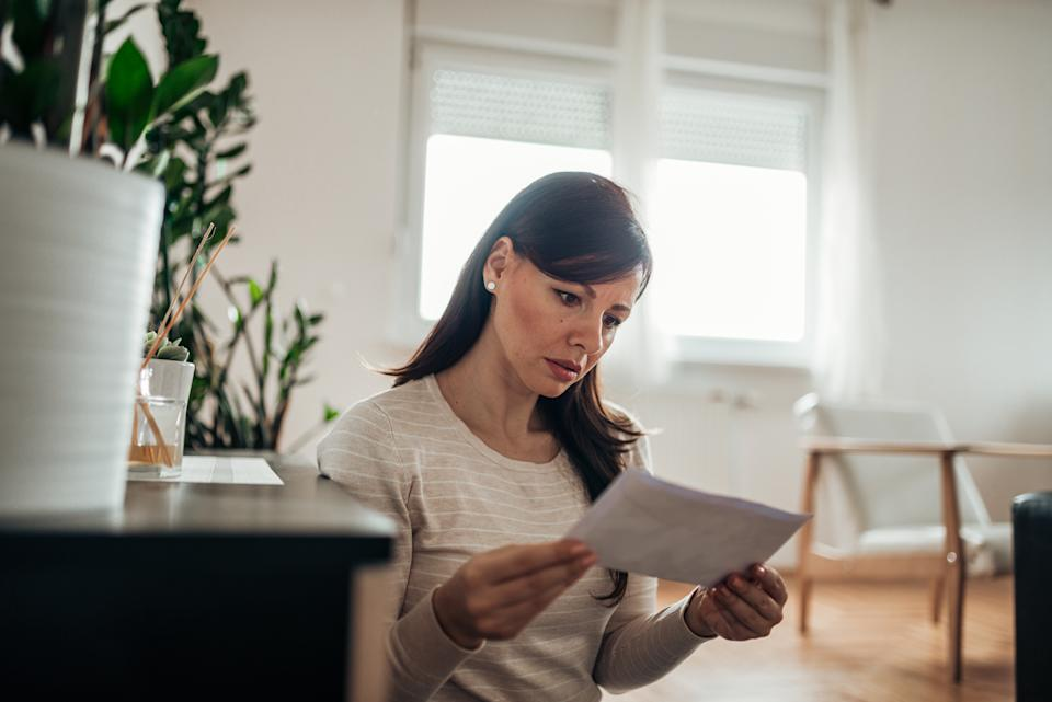 Worried woman reading a letter at home.