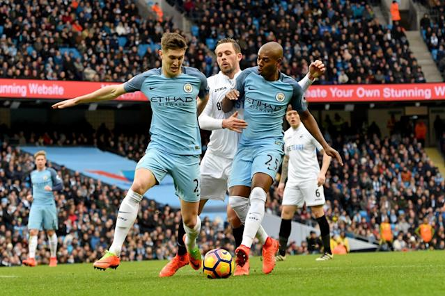 <p>Swansea City's Gylfi Sigurdsson is tackled by Manchester City's John Stones (left) and Manchester City's Fernandinho (right) during the Premier League match between Manchester City and Swansea City at the Etihad Stadium on February 5, Manchester, England. </p>
