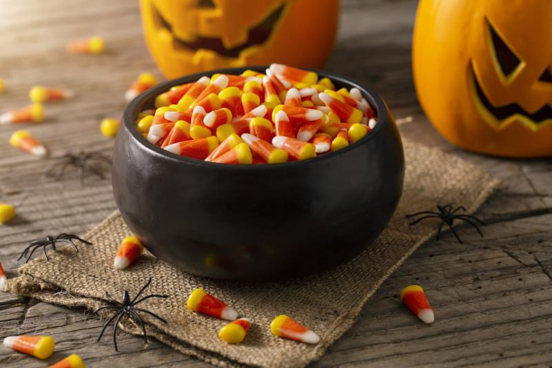 Bowl of Halloween candy corns with jack o' lanterns and spider decoration on rustic wood table.