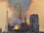 """FILE - In this file photo dated Monday, April 15, 2019, with the Eiffel Tower behind, left, flames and smoke rise from the blaze at Notre Dame Cathedral in Paris that destroyed its spire and its roof but spared its twin medieval bell towers, and prompted a frantic rescue effort to save its most precious artefacts. The recent devastating Notre Dame fire in Paris was a warning bell that all of Europe needs to hear, since so many monuments and palaces across the continent are in need of better upkeep according to European officials. """"We are so used to our outstanding cultural heritage in Europe that we tend to forget that it needs constant care and attention,"""" Tibor Navracsics, the European Union's top culture official, told The Associated Press. (AP Photo/Thierry Mallet, FILE)"""