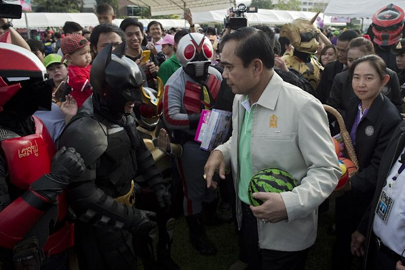 Thai Prime Minister, General Prayut Chan-O-Cha, meets with comics superheroes during a Children's Day event in Bangkok, on January 9, 2016 (AFP Photo/Nicolas Asfouri)