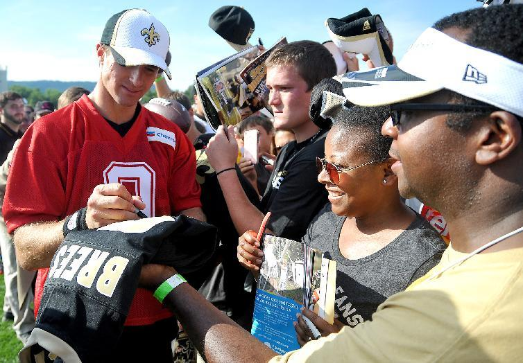 New Orleans Saints quarterback Drew Brees signs autographs for fans during NFL football training camp in White Sulphur Springs, W.Va., Saturday, July 26, 2014