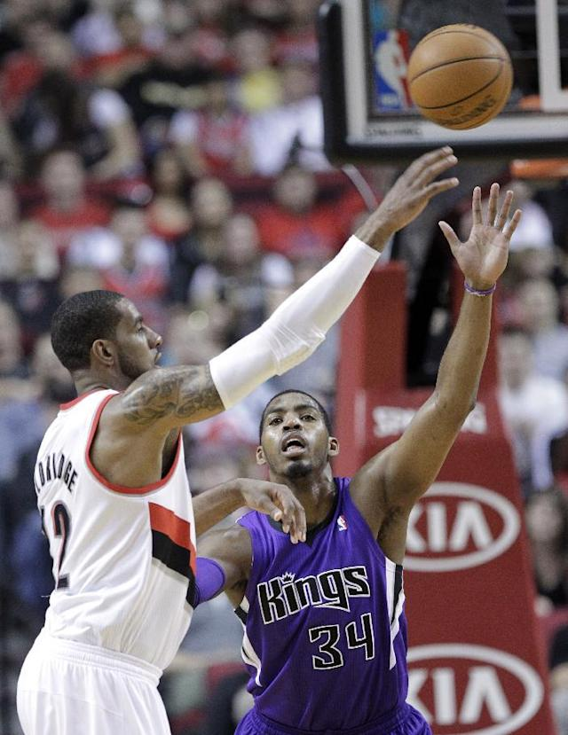 Portland Trail Blazers forward LaMarcus Aldridge, left, passes against Sacramento Kings forward Jason Thompson during the first half of an NBA basketball game in Portland, Ore., Wednesday, April 9, 2014. (AP Photo/Don Ryan)