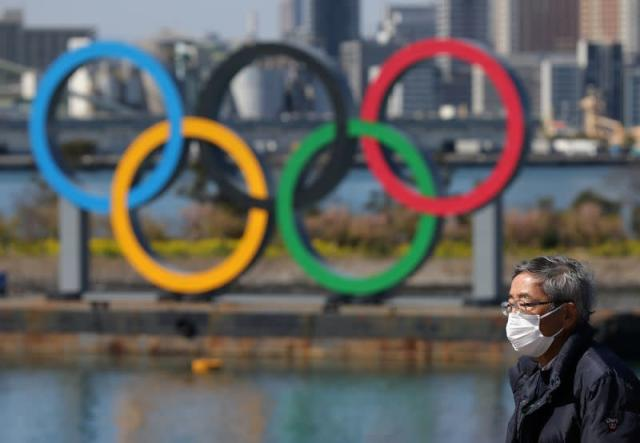 Man walks in front of the Giant Olympic rings at the waterfront area at Odaiba Marine Park in Tokyo
