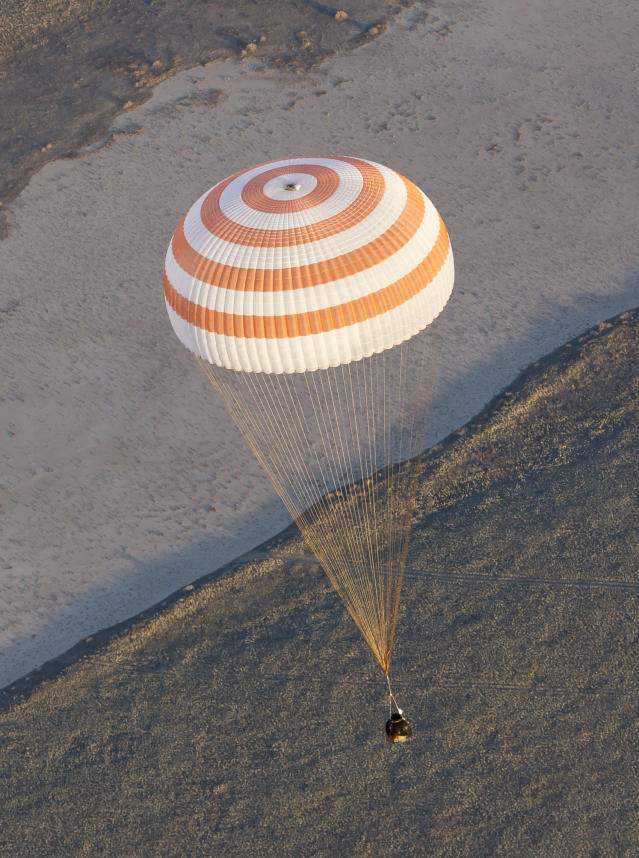Soyuz TMA-09M capsule carrying the International Space Station (ISS) crew members, Fyodor Yurchikhin of Russia, Karen Nyberg of the United States and Luca Parmitano of Italy, descends with a parachute before landing in a remote area near the town of Zhezkazgan in central Kazakhstan Monday, Nov. 11, 2013. The Russian space capsule carrying the Sochi Olympic torch and the three astronauts returned to Earth on Monday from the ISS in a flawless landing on the steppes of Kazakhstan. (AP Photo/Shamil Zhumatov, Pool)