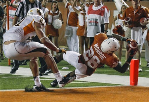 Texas' D.J. Monroe (26) scores a touchdown past Wyoming defender Mark Nzeocha during the second quarter of an NCAA college football game, Saturday, Sept. 1, 2012, in Austin, Texas.(AP Photo/Jack Plunkett)