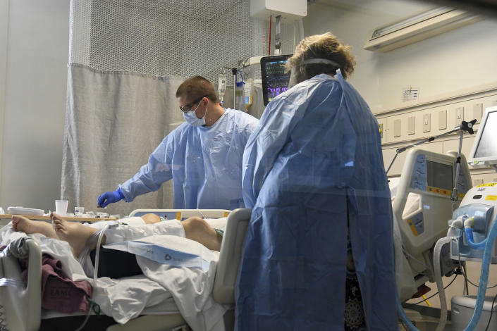 Nurse Jesse Phelps, left, works on a COVID-19 patient as a family member looks on at East Alabama Medical Center in the intensive care unit Thursday, Dec. 10, 2020, in Opelika, Ala. The medical center faces a new influx of COVID-19 patients as the pandemic intensifies. (AP Photo/Julie Bennett)