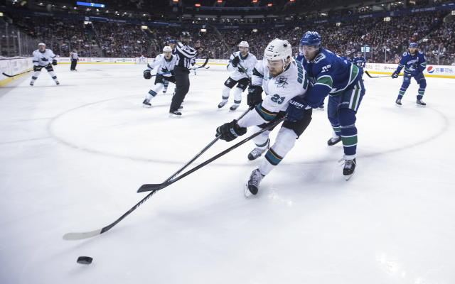 San Jose Sharks' Barclay Goodrow (23) is checked by Vancouver Canucks' Ben Hutton (27) during the first period of an NHL hockey game in Vancouver, British Columbia, on Monday, Feb. 11, 2019. (Darryl Dyck/The Canadian Press via AP)