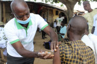 A Muslim faithful is administered a Moderna COVD-19 vaccination outside the Kuje, Central Mosque outskirts of Abuja, Friday, Oct. 8, 2021. Nigeria has begun the second rollout of COVID-19 vaccines as it aims to protect its population of more than 200 million amid an infection surge in a third wave of the pandemic. (AP Photo/Gbemiga Olamikan)