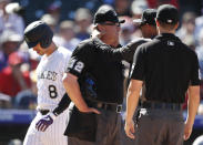 Home plate umpire Gerry Davis (12) is checked by Colorado Rockies trainer Keith Dugger after Davis was hit in the head by a foul ball off the bat of Josh Fuentes in the fourth inning of a baseball game against the St. Louis Cardinals Thursday, Sept. 12, 2019, in Denver. (AP Photo/David Zalubowski)