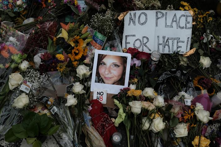 "A photograph of Charlottesville victim Heather Heyer is seen amongst flowers left at the scene of the car attack on a group of counter-protesters that took her life  during the ""Unite the Right"" rally as people continue to react to the weekend violence in Charlottesville, Virginia, August 14, 2017.  (Justin Ide/Reuters)"