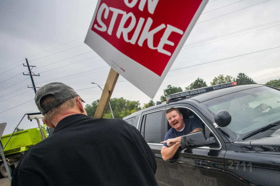 Flint Police ask protestors to let traffic through in larger waves as General Motors employees stand with United Auto Workers members and labor supporters outside of the Flint Metal Center as part of the national UAW strike against GM on Monday, Sept. 16, 2019 in Flint, Mich. Thousands of members of the United Auto Workers walked off General Motors factory floors or set up picket lines early Monday as contract talks with the company deteriorated into a strike. (Jake May/The Flint Journal via AP)