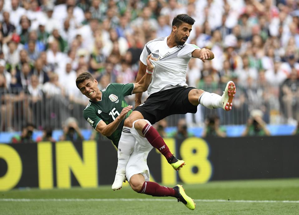 <p>Germany's midfielder Sami Khedira (R) and Mexico's defender Hector Moreno (L) fall after attempting to head the ball during the Russia 2018 World Cup Group F football match between Germany and Mexico at the Luzhniki Stadium in Moscow on June 17, 2018. (Photo by Patrik STOLLARZ / AFP) </p>