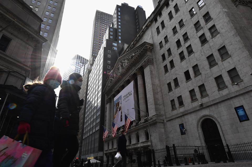 People walk past the New York Stock Exchange (NYSE) at Wall Street on February 17, 2021 in New York City. - Wall Street stocks retreated early Wednesday as worries about potentially higher inflation accompanied much better-than-expected US retail sales. (Photo by Angela Weiss / AFP) (Photo by ANGELA WEISS/AFP via Getty Images)