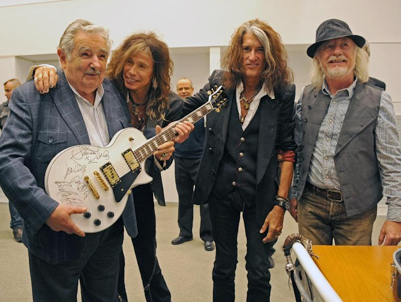 In this picture released by Uruguay's Press Office, President Jose Mujica, left, poses with Aerosmith's band members Steven Tyler, second from left, Joe Perry, second from right, and Brad Whitford after receiving an autographed guitar as a gift at presidential house in Montevideo, Uruguay, Tuesday, Oct. 8, 2013. The band will perform Wednesday as part of their Latin America tour. (AP Photo/Uruguay Press Office, Alvaro Salas)