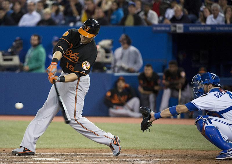 Baltimore Orioles' Chris Davis hits a solo home run as Toronto Blue Jays catcher J.P. Arencibia watches during the eighth inning of a baseball game in Toronto on Friday, Sept. 13, 2013. (AP Photo/The Canadian Press, Nathan Denette)