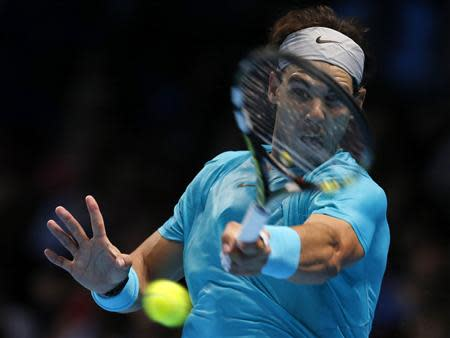 Rafael Nadal of Spain hits a return during his men's singles tennis match against Stanislas Wawrinka of Switzerland at the ATP World Tour Finals at the O2 Arena in London November 6, 2013. REUTERS/Suzanne Plunkett