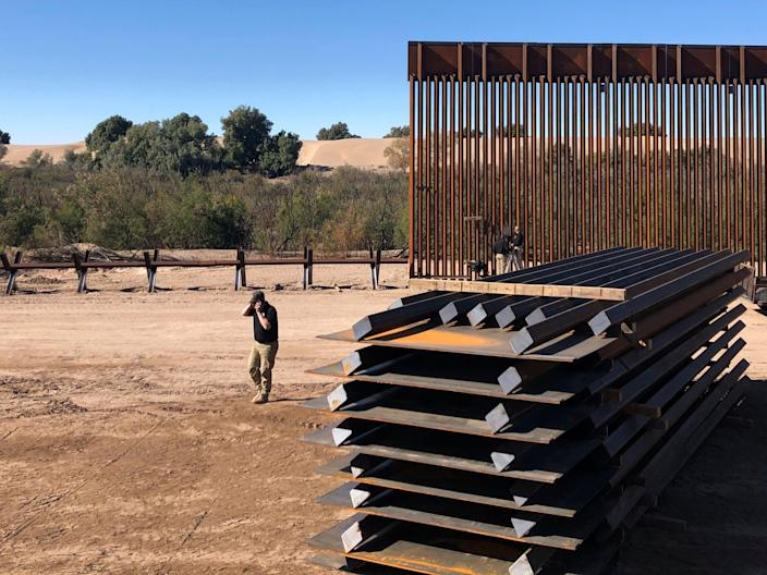 A man passes new border wall sections, right, as they replace the old fencing, left, Friday, Jan. 10, 2020, near Yuma, Arizona (AP)