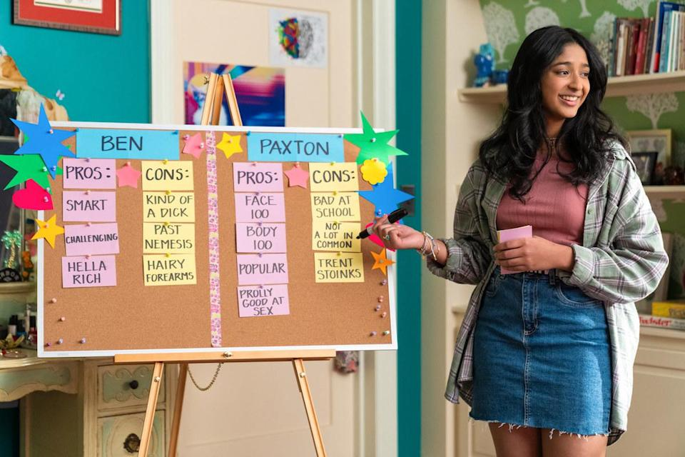 Devi standing in front of a board listing the pros and cons of dating Ben or Paxton