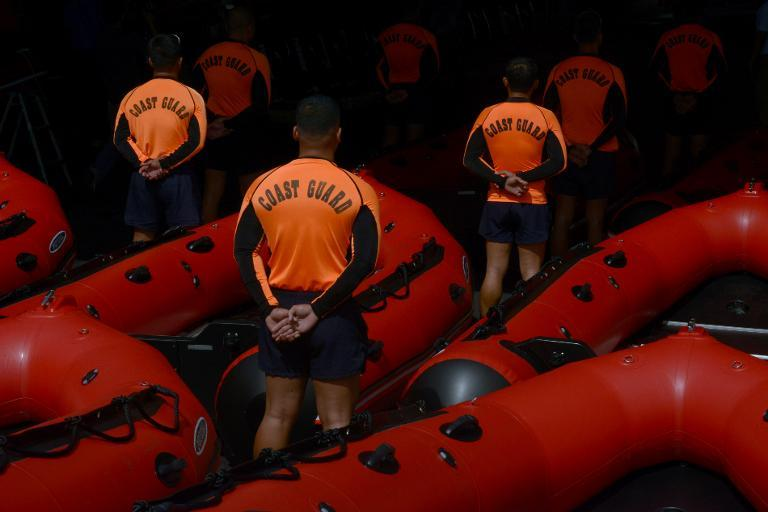 Philippine Coast Guard (PCG) personnel stand in formation beside newly-acquired rubber boats following a blessing ceremony in Manila on November 6, 2013