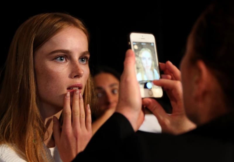 A model is photographed on a cell phone after her makeup is completed before dressing for the Tommy Hilfiger presentation during New York Fashion Week (AFP Photo/Trevor Collens)