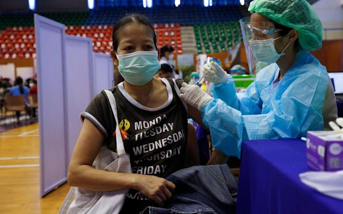 A woman receives a dose of AstraZeneca vaccine at a gymnasium turned vaccination center in Bangkok, Thailand - RUNGROJ YONGRIT/EPA-EFE/Shutterstock