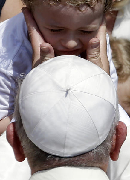 Pope Francis caresses a child after he delivered the Angelus prayer at the Pontiff's residence of Castel Gandolfo, near Rome, Sunday July 14, 2013. For a day, Pope Francis has abandoned his traditional Sunday greeting at the Vatican, opting for an informal front-door encounter in a hill town outside Rome which hosts the papal summer residence. Unlike his predecessors, Francis isn't staying in Castel Gandolfo for the summer, but came for the day. (AP Photo/Gregorio Borgia)