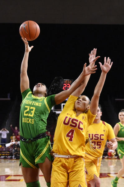 Oregon guard Minyon Moore, left, shoots as Southern California guard Endyia Rogers defends during the first half of an NCAA college basketball game Sunday, Feb. 16, 2020, in Los Angeles. (AP Photo/Mark J. Terrill)