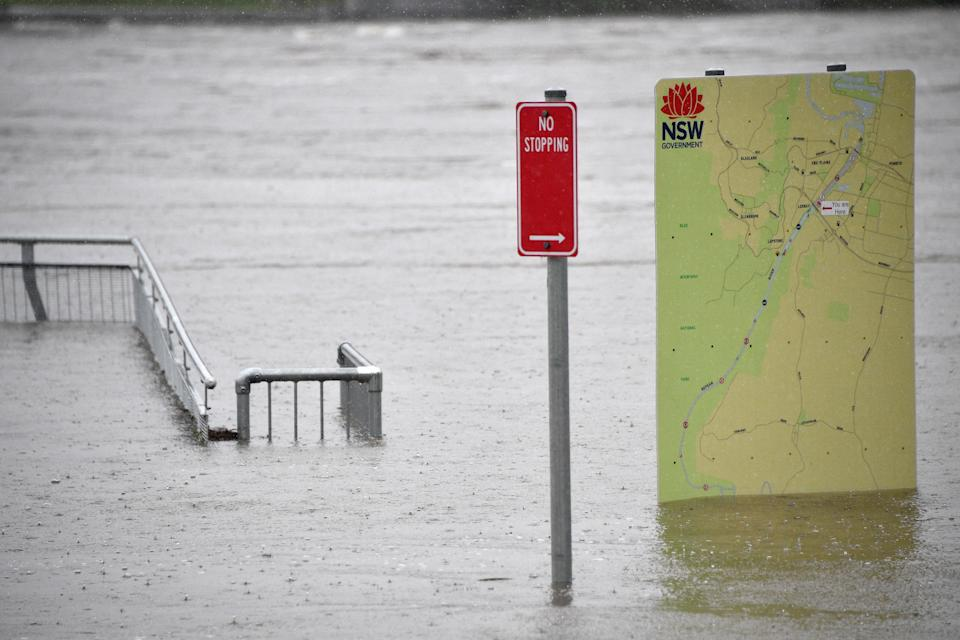 This picture shows sign boards in a flooded park along the overflowing Nepean river in Penrith suburb on March 21, 2021, as Sydney braced for its worst flooding in decades after record rainfall caused its largest dam to overflow and as deluges prompted mandatory mass evacuation orders along Australia's east coast. (Photo by Saeed KHAN / AFP) (Photo by SAEED KHAN/AFP via Getty Images)