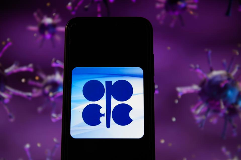 POLAND - 2020/04/28: In this photo illustration an OPEC logo displayed on a smartphone with a COVID 19 sample image in the background. (Photo Illustration by Omar Marques/SOPA Images/LightRocket via Getty Images)