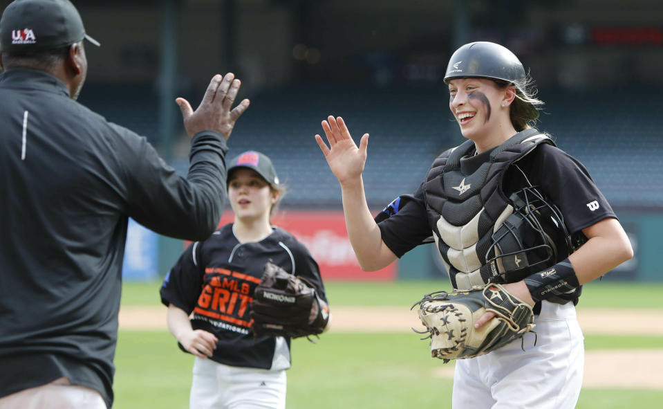 Catcher Audrey Byrne, right, gets a high-five after the third out during baseball game in Arlington, Texas, Friday, March 8, 2019. More than 60 high school girls from the United States, as well as Canada and Puerto Rico are taking part in the inaugural MLB Grit event, a tournament specifically for girls who play baseball. (AP Photo/LM Otero)