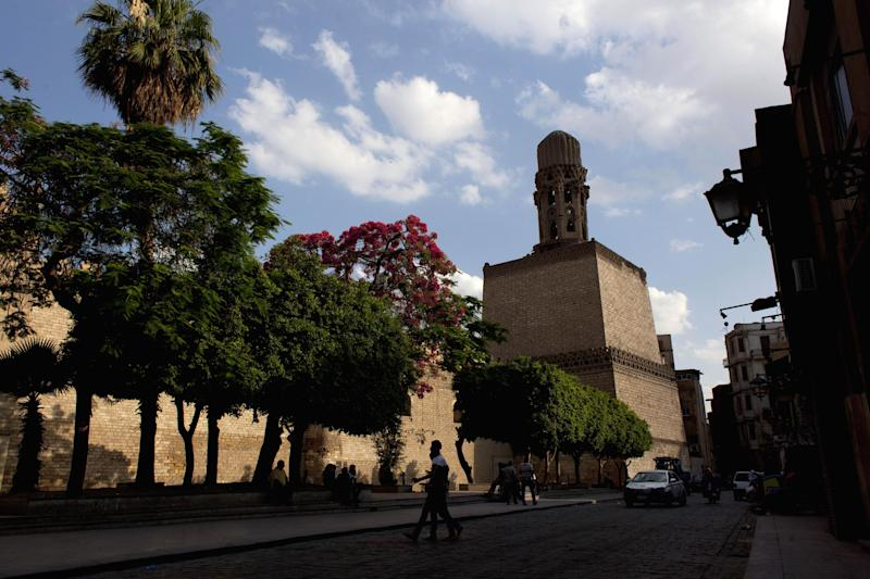 In this photo taken Sunday, May 12, 2013, Egyptians walk by the medieval fortress wall in the historic Fatimid Cairo, Egypt. Cairo, the Arab world's most populated city, is often referred to as an open-air museum of Islamic antiquities and the city of 1,000 minarets. But its rich history and contributions to Islamic art has languished. (AP Photo/Nasser Nasser)