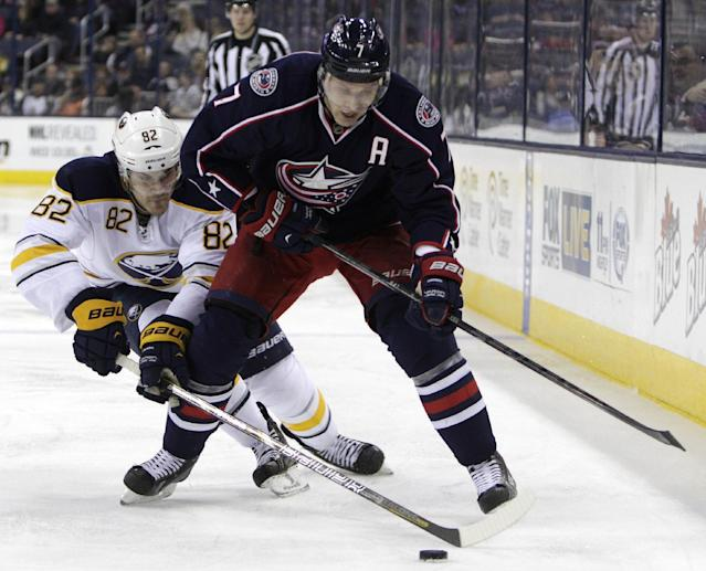 Columbus Blue Jackets' Jack Johnson, right, tries to control the puck as Buffalo Sabres' Marcus Foligno defends during the second period of an NHL hockey game, Saturday, Jan. 25, 2014, in Columbus, Ohio. (AP Photo/Jay LaPrete)